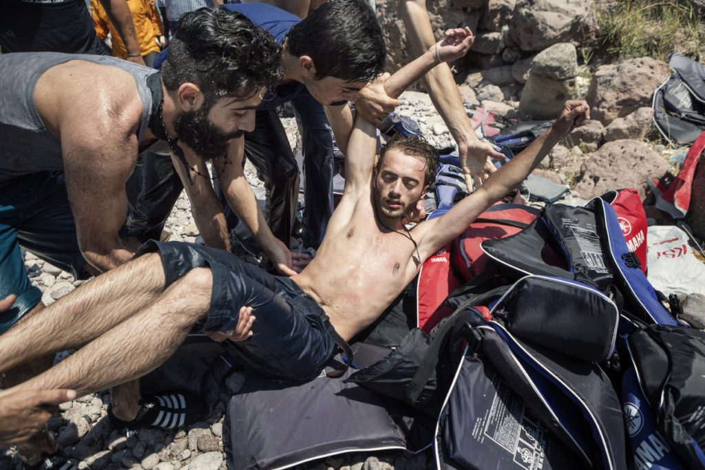 2015. Lesvos. Greece. A group of Syrians help a fellow Syrian who was taken ill after he swam to reach the shore of the Greek island of Lesvos.